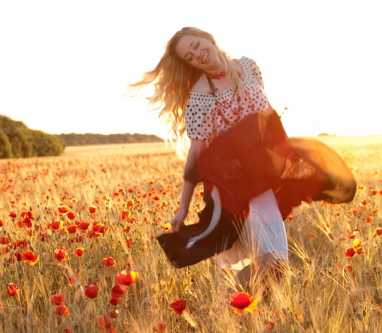 Beautiful blonde lady walking in poppy field on sunset